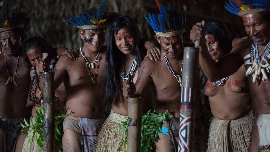 In this May 24, 2014, photo, men and women from various tribes dance in the Tatuyo indigenous community near Manaus, Brazil. The community of thatched palm roofed houses is home to nine families who moved to the riverside plot some 15 years ago from deep inside the rainforest. While they normally wear the shorts, t-shirts and flip-flops that are standard fare throughout Brazil, the villagers change into their ceremonial finest to receive tourists. (AP Photo/Felipe Dana)
