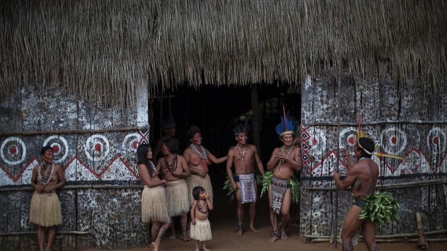 In this May 19, 2014 photo, residents from various tribes stand at the entrance of a traditionally built house in the Tatuyo indigenous community near Manaus, Brazil. While they normally wear the shorts, t-shirts and flip-flops that are standard fare throughout Brazil, the villagers change into their ceremonial finest to receive the tourists, the men and boys donning loincloths embellished in the back with bunches of freshly cut leaves and rattling anklets made from hollow seeds, the women and girls wearing graceful skirts of dried grass. (AP Photo/Felipe Dana)
