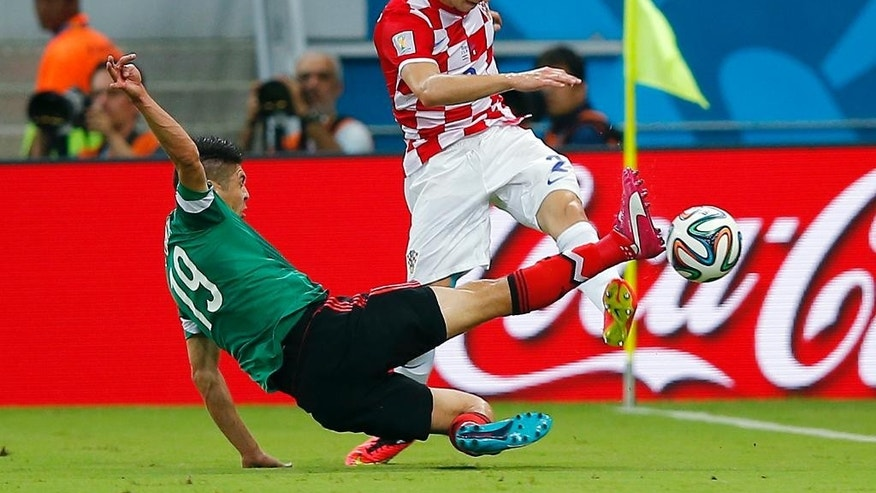 Mexico's Oribe Peralta, left, fights for the ball with Croatia's Sime Vrsaljko during the group A World Cup soccer match between Croatia and Mexico at the Arena Pernambuco in Recife, Brazil, Monday, June 23, 2014. (AP Photo/Eduardo Verdugo)