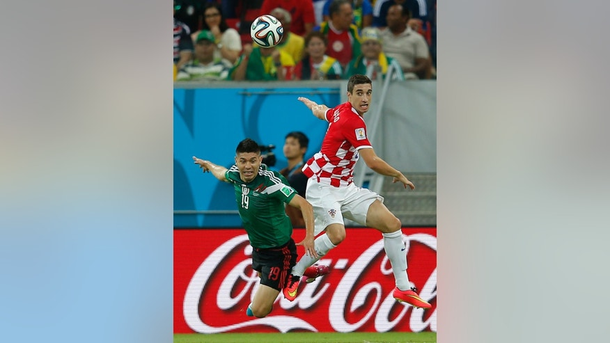 Mexico's Oribe Peralta heads the ball next to Croatia's Sime Vrsaljko during the group A World Cup soccer match between Croatia and Mexico at the Arena Pernambuco in Recife, Brazil, Monday, June 23, 2014. (AP Photo/Eduardo Verdugo)
