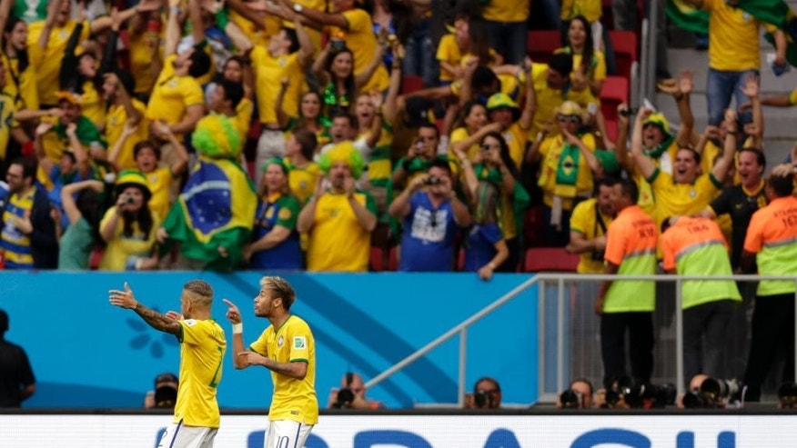 Brazil's Neymar, second left, celebrates scoring the opening goal during the group A World Cup soccer match between Cameroon and Brazil at the Estadio Nacional in Brasilia, Brazil, Monday, June 23, 2014. (AP Photo/Dolores Ochoa)