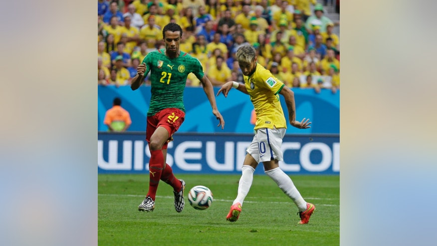Brazil's Neymar kicks the ball past Cameroon's Joel Matip to score his side's first goal during the group A World Cup soccer match between Cameroon and Brazil at the Estadio Nacional in Brasilia, Brazil, Monday, June 23, 2014. (AP Photo/Natacha Pisarenko)
