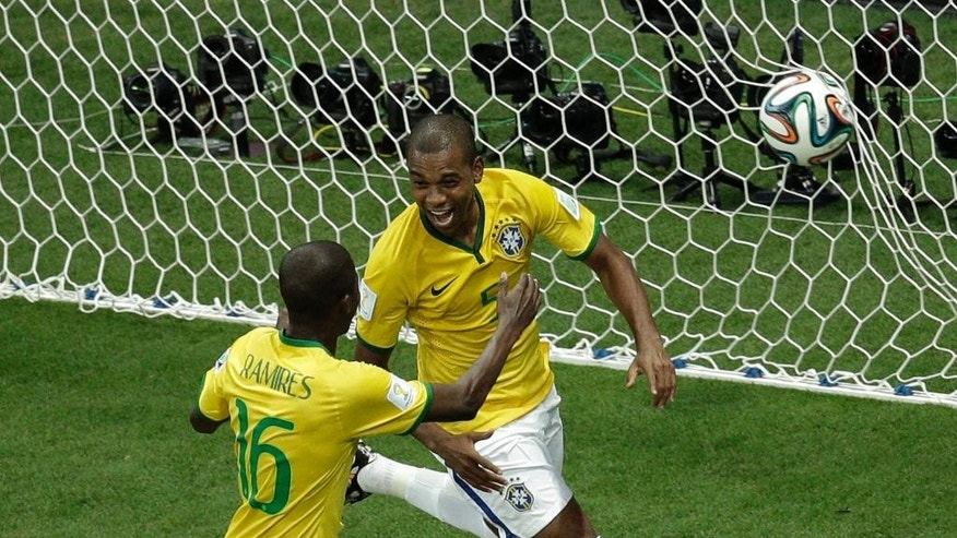 Brazil's Fernandinho, right, celebrates scoring his side's 5th goal during the group A World Cup soccer match between Cameroon and Brazil at the Estadio Nacional in Brasilia, Brazil, Monday, June 23, 2014. (AP Photo/Christophe Ena)