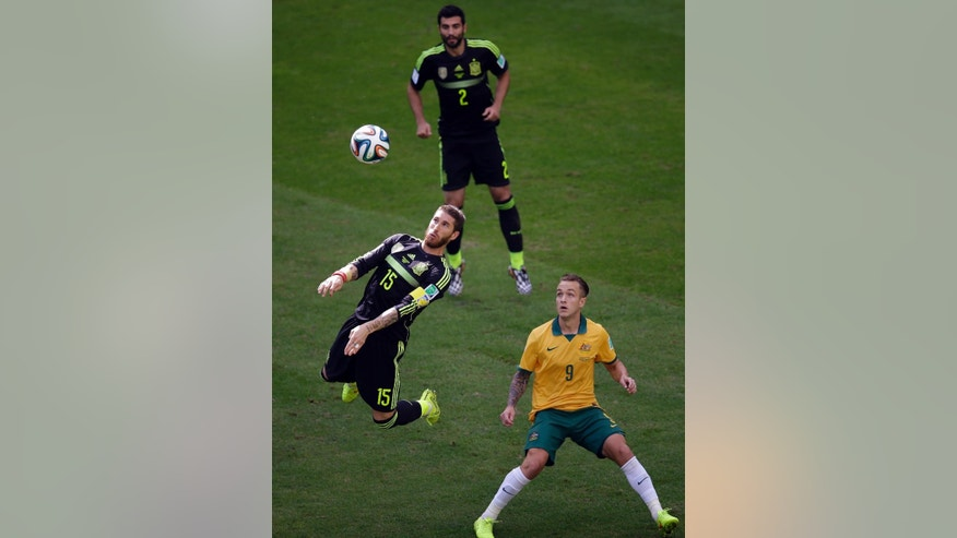 Spain's Sergio Ramos, left, goes for a header ad Australia's Adam Taggart, right, and Spain's Raul Albiol watch him, during the group B World Cup soccer match between Australia and Spain at the Arena da Baixada in Curitiba, Brazil, Monday, June 23, 2014. (AP Photo/Michael Sohn)