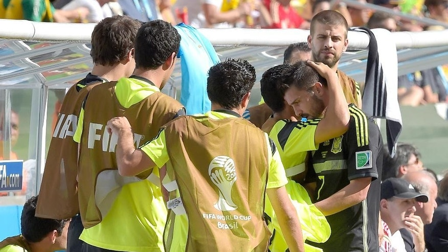 Spain's David Villa, right, is comforted by teammates as he leaves the pitch during the group B World Cup soccer match between Australia and Spain at the Arena da Baixada in Curitiba, Brazil, Monday, June 23, 2014. (AP Photo/Manu Fernandez)