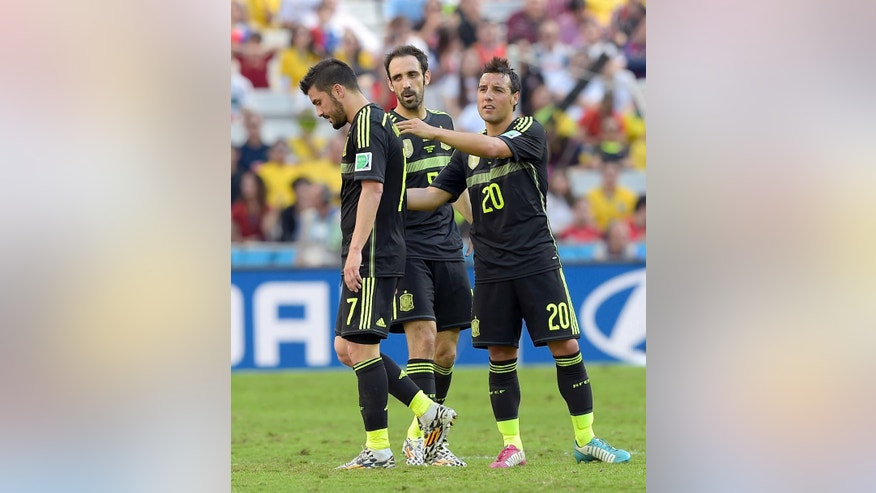 Spain's Santi Cazorla comforts Spain's David Villa as he leaves the pitch during the group B World Cup soccer match between Australia and Spain at the Arena da Baixada in Curitiba, Brazil, Monday, June 23, 2014. Center is Spain's Juanfran.(AP Photo/Manu Fernandez)