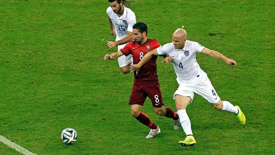 Portugal's Joao Moutinho is challenged by United States' Michael Bradley, right, and Kyle Beckerman, left, during the group G World Cup soccer match between the USA and Portugal at the Arena da Amazonia in Manaus, Brazil, Sunday, June 22, 2014. (AP Photo/Themba Hadebe)
