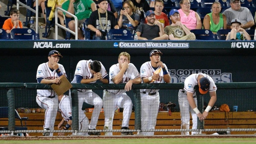 Virginia players watch as Vanderbilt defeated Virginia 9-8 in the opening game of the best-of-three NCAA baseball College World Series finals in Omaha, Neb., Monday, June 23, 2014. (AP Photo/Ted Kirk)