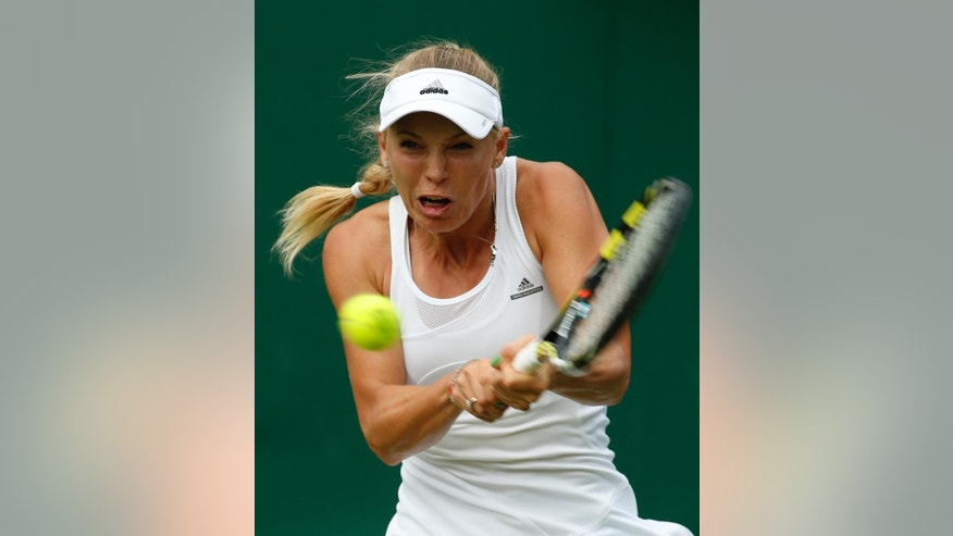 Caroline Wozniacki of Denmark plays a return to Shahar Peer of Israel during their first round match at the All England Lawn Tennis Championships in Wimbledon, London,  Monday, June  23, 2014. (AP Photo/Alastair Grant)