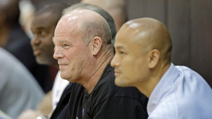 Charlotte Hornets head coach Steve Clifford, left, and general manager Rich Cho, right, watch players during an NBA draft basketball workout in Charlotte, N.C., Tuesday, June 24, 2014. (AP Photo/Chuck Burton)