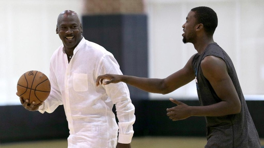 Charlotte Hornets owner Michael Jordan, left, jokes with forward Michael Kidd-Gilchrist, right, during an NBA draft basketball workout in Charlotte, N.C., Tuesday, June 24, 2014. (AP Photo/Chuck Burton)