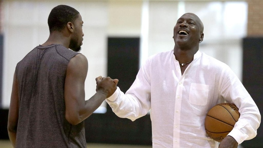 Charlotte Hornets owner Michael Jordan, right, laughs with forward Michael Kidd-Gilchrist, left, during an NBA draft basketball workout in Charlotte, N.C., Tuesday, June 24, 2014. (AP Photo/Chuck Burton)