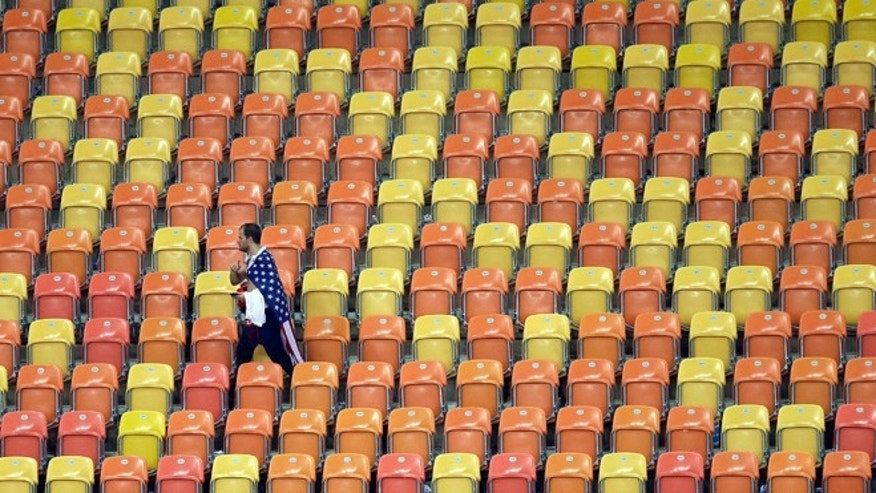 A US fan leaves the stands after a 2-2 draw in the group G World Cup soccer match between the USA and Portugal at the Arena da Amazonia in Manaus, Brazil, Sunday, June 22, 2014. (AP Photo/Themba Hadebe)