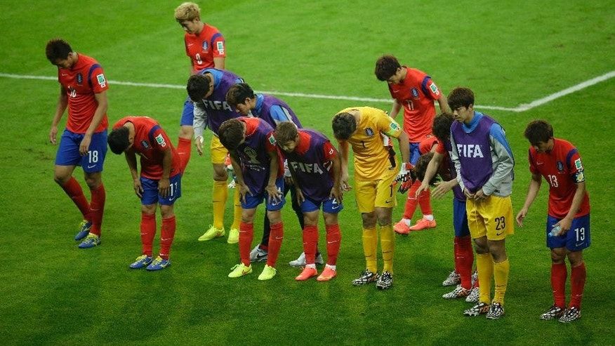 Members of the South Korean soccer team bowas they leave the pitch after they lost 2-4 in the group H World Cup soccer match between South Korea and Algeria at the Estadio Beira-Rio in Porto Alegre, Brazil, Sunday, June 22, 2014. (AP Photo/Michael Sohn)