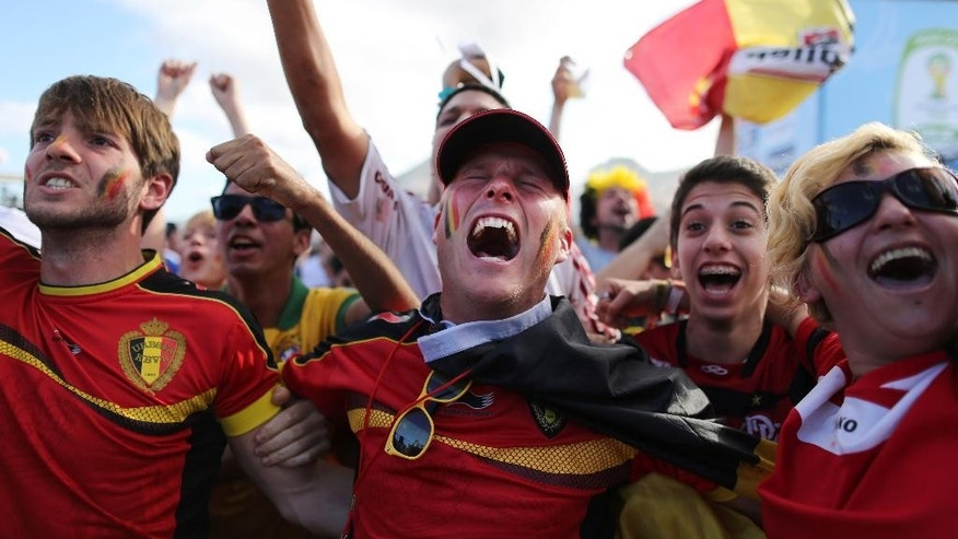 Soccer fans celebrate the goal scored by Belgium as they watch a live broadcast of the group H World Cup match between Belgium and Russia inside the FIFA Fan Fest area on Copacabana beach, in Rio de Janeiro, Brazil, Sunday, June 22, 2014. Teenage forward Divock Origi scored in the 88th minute as Belgium beat Russia 1-0 Sunday to secure a spot in the second round of the international soccer tournament. (AP Photo/Leo Correa)