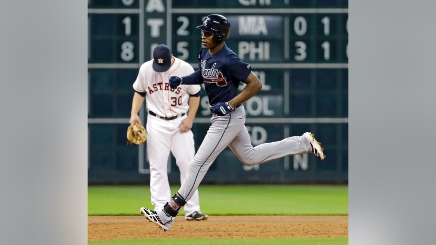 Atlanta Braves' B.J. Upton, right, runs past Houston Astros third baseman Matt Dominguez (30) after hitting a home run during the third inning of a baseball game Tuesday, June 24, 2014, in Houston. (AP Photo/David J. Phillip)