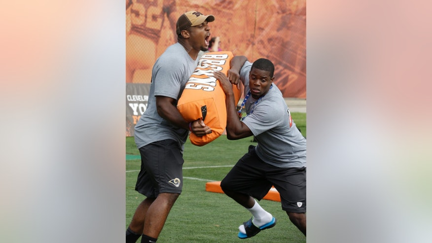 St. Louis Rams' Michael Sam, left, tries to stop a participant during an NFL football Play 60 youth event, part of the NFL's annual Rookie Symposium, at the Cleveland Browns practice facility Tuesday, June 24, 2014, in Berea, Ohio. (AP Photo/Tony Dejak)
