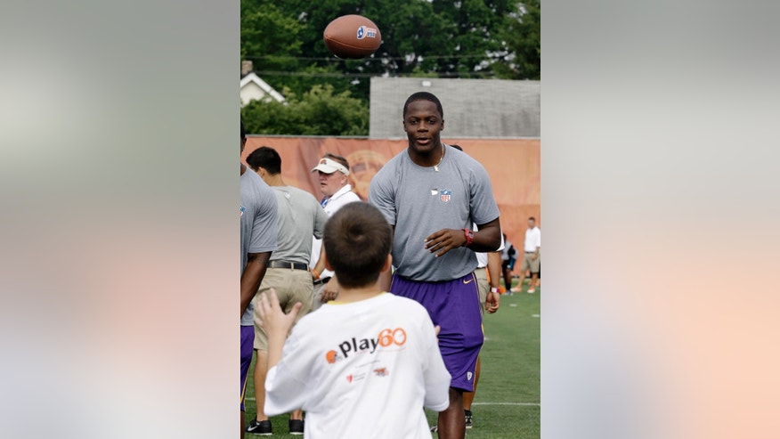 Minnesota Vikings NFC rookie Teddy Bridgewater tosses the ball to a participant during an NFL football Play 60 youth, part of the NFL's annual Rookie Symposium, at the Cleveland Browns practice facility Tuesday, June 24, 2014, in Berea, Ohio. (AP Photo/Tony Dejak)