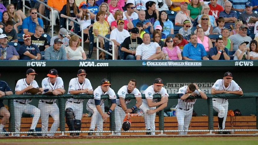 Virginia players watch from the bench in the third inning of the opening game of the best-of-three NCAA baseball College World Series finals against Vanderbilt in Omaha, Neb., Monday, June 23, 2014. (AP Photo/Ted Kirk)