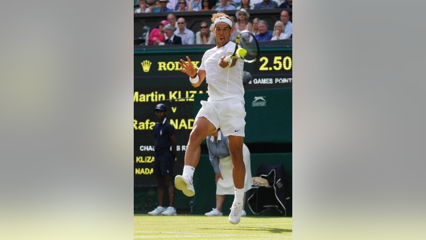 Rafael Nadal of Spain plays a return to Martin Klizan of Slovakia during their match at the All England Lawn Tennis Championships in Wimbledon, London, Tuesday, June 24, 2014. (AP Photo/Sang Tan)