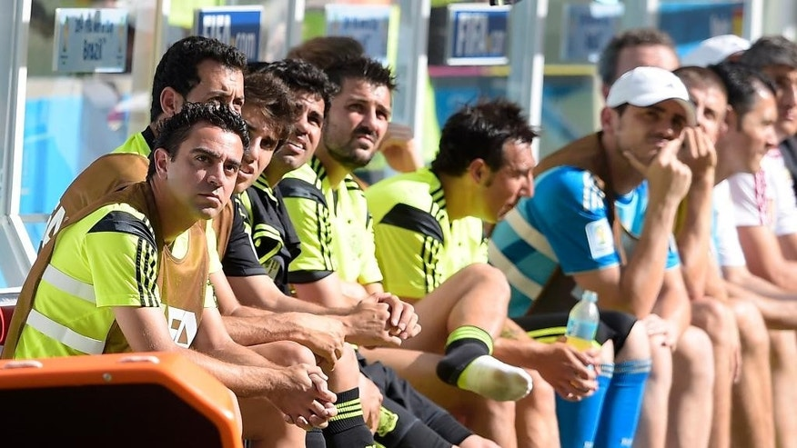 Spain's Xavi, left, sits on the bench with teammates during the group B World Cup soccer match between Australia and Spain at the Arena da Baixada in Curitiba, Brazil, Monday, June 23, 2014. Center is Spain's David Villa.(AP Photo/Manu Fernandez)
