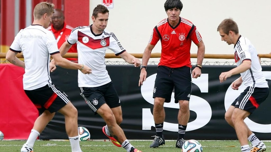 German national soccer players Tonis Kroos, from left, Miroslav Klose, head coach Joachim Loew and captain Philipp Lahm challenge for the ball during a training session in Santo Andre near Porto Seguro, Brazil, Monday, June 23, 2014. Germany play in group G of the 2014 soccer World Cup. (AP Photo/Matthias Schrader)