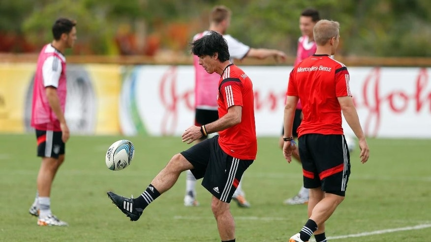 German national soccer team head coach Joachim Loew kicks a football during a training session in Santo Andre near Porto Seguro, Brazil, Monday, June 23, 2014. Germany play in group G of the 2014 soccer World Cup. (AP Photo/Matthias Schrader)