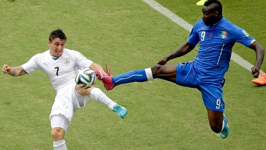 June 24, 2014: Italy's Mario Balotelli (9) and Uruguay's Cristian Rodriguez (7) battle for the ball during the group D World Cup soccer match between Italy and Uruguay at the Arena das Dunas in Natal, Brazil.