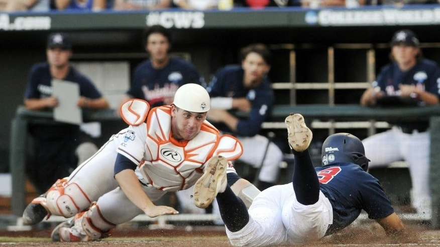 Vanderbilt's Zander Wiel, right, slides safely into home plate for a run against Virginia catcher Nate Irving in the third inning of game one of the best-of-three NCAA baseball College World Series finals in Omaha, Neb., Monday, June 23, 2014.  (AP Photo/Eric Francis)