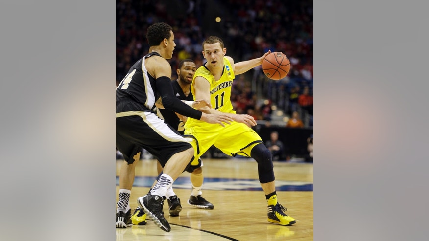 FILE - In this March 20, 2014 file photo, Michigan guard Nik Stauskas (11) drives the ball during the second half of a second round NCAA college basketball tournament game against Wofford in Milwaukee. Eight Canadians could be selected in the NBA draft on Thursday, June 26, 2014. Andrew Wiggins, Stauskas and Tyler Ennis are expected to go in the first round. (AP Photo/Jeffrey Phelps, File)