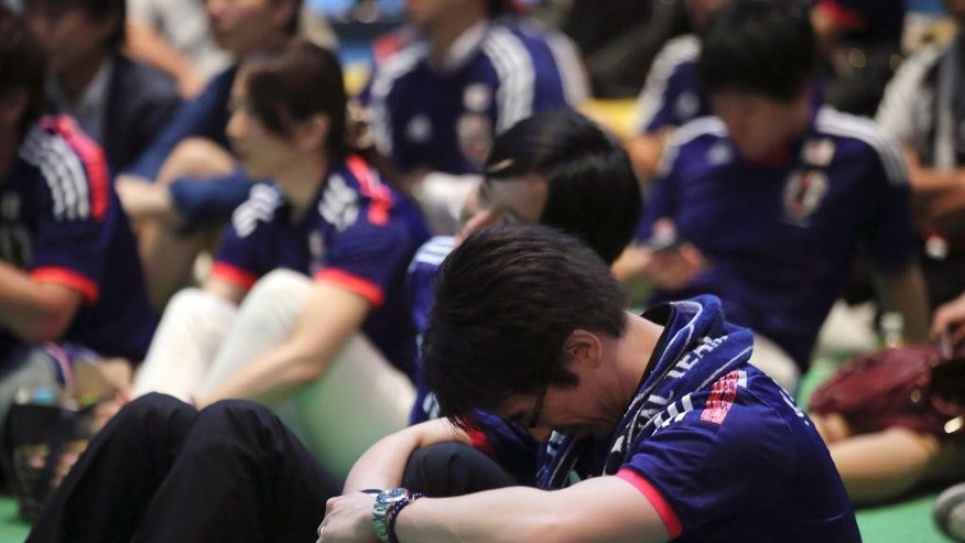 Japanese soccer fans are dejected after watching a live broadcasting of the group C World Cup soccer match between Japan and Colombia at a public viewing venue in Tokyo, Wednesday, June 25, 2014. Colombia  won 4-1. (AP Photo/Eugene Hoshiko)