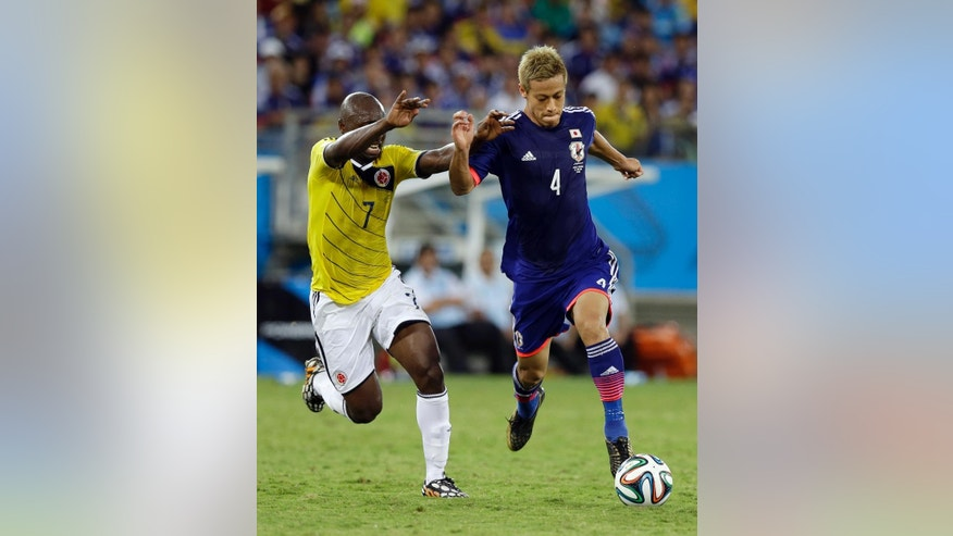 Colombia's Pablo Armero, left, challenges Japan's Keisuke Honda during the group C World Cup soccer match between Japan and Colombia at the Arena Pantanal in Cuiaba, Brazil, Tuesday, June 24, 2014. (AP Photo/Thanassis Stavrakis)