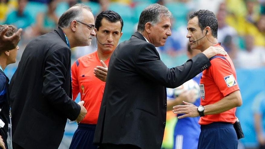 Iran's head coach Carlos Queiroz, center, puts his hands on the shoulders of referee Carlos Velasco Carballo of Spain during the group F World Cup soccer match between Bosnia and Iran at the Arena Fonte Nova in Salvador, Brazil, Wednesday, June 25, 2014. (AP Photo/Sergei Grits)