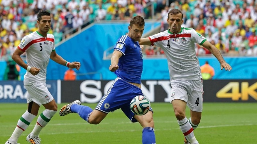 Bosnia's Edin Dzeko, center, gets in a shot despite the challenge of Iran's Jalal Hosseini, right, during the group F World Cup soccer match between Bosnia and Iran at the Arena Fonte Nova in Salvador, Brazil, Wednesday, June 25, 2014. (AP Photo/Sergei Grits)