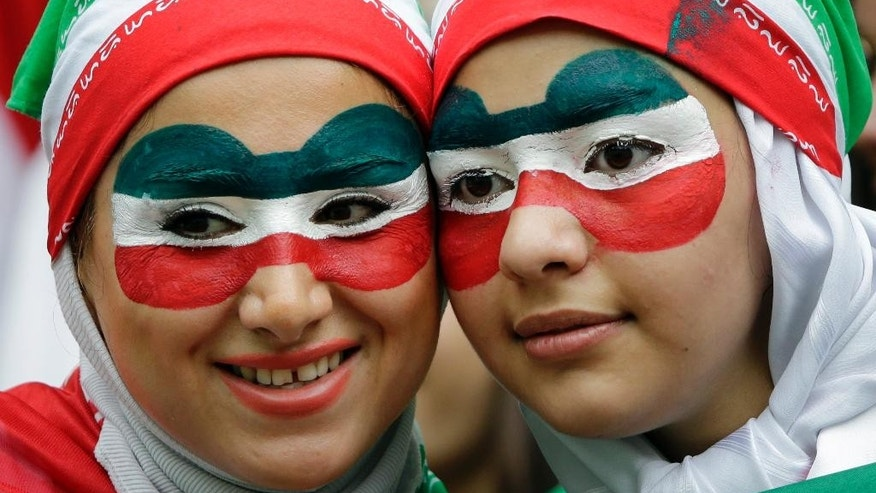 Iranian fans wait for the start of the group F World Cup soccer match between Bosnia and Iran at the Arena Fonte Nova in Salvador, Brazil, Wednesday, June 25, 2014. (AP Photo/Sergei Grits)