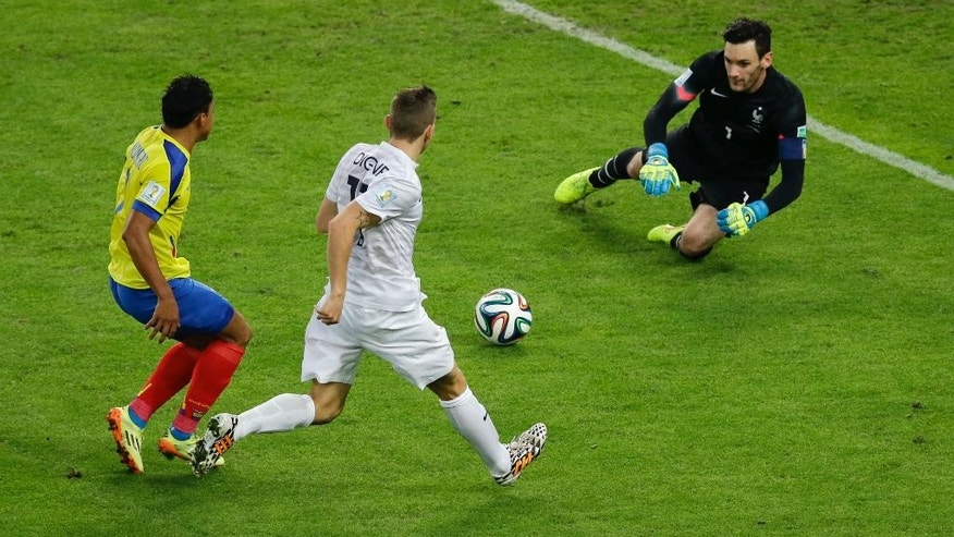 Ecuador's Jefferson Montero, left, takes a shot which is saved by France's goalkeeper Hugo Lloris as France's Lucas Digne, center, moves in during the group E World Cup soccer match between Ecuador and France at the Maracana Stadium in Rio de Janeiro, Brazil, Wednesday, June 25, 2014. (AP Photo/Andrew Medichini)