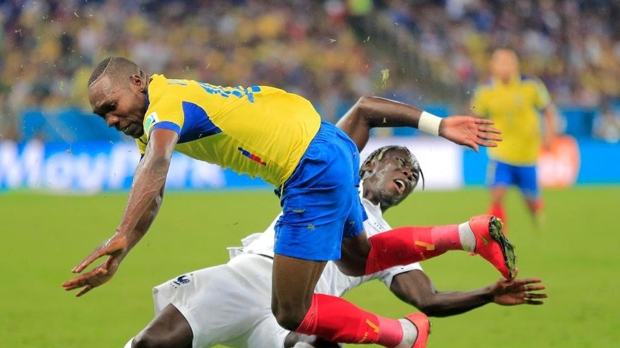 Ecuador's Walter Ayovi collides with France's Bacary Sagna during the group E World Cup soccer match between Ecuador and France at the Maracana Stadium in Rio de Janeiro, Brazil, Wednesday, June 25, 2014. (AP Photo/Bernat Armangue)