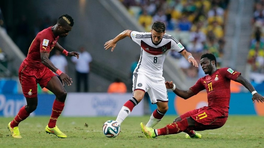 Germany's Mesut Ozil, center, is challenged by Ghana's Sulley Muntari, right, during the group G World Cup soccer match at the Arena Castelao in Fortaleza, Brazil, Saturday, June 21, 2014. (AP Photo/Matthias Schrader)