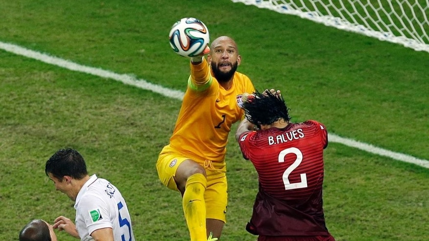 United States' goalkeeper Tim Howard, center, reaches a ball ahead of Portugal's Bruno Alves, right, during the group G World Cup soccer match between the USA and Portugal at the Arena da Amazonia in Manaus, Brazil, Sunday, June 22, 2014. (AP Photo/Themba Hadebe)