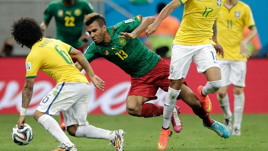 Cameroon's Maxim Choupo-Moting (13) is tripped in front of Brazil's Luiz Gustavo (17) and Brazil's Marcelo (6) during the group A World Cup soccer match between Cameroon and Brazil at the Estadio Nacional in Brasilia, Brazil, Monday, June 23, 2014. (AP Photo/Bernat Armangue)