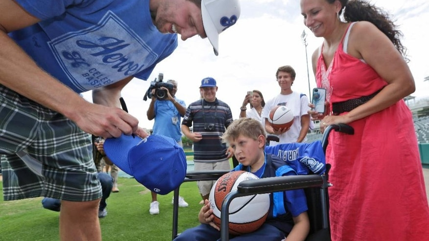 Dallas Mavericks center Dirk Nowitzki, of Germany,  sign as autograph for Kyle Murray, 10, as his mother Elizabeth Murray looks on before practice for a charity baseball game Friday, June 20, 2014, in Frisco, Texas.  Murray suffers from an aggressive brain cancer. Nowitzki will host an annual baseball game on Saturday to benefit the children's charities of the Dirk Nowitzki Foundation and the Heroes Foundation.  (AP Photo/LM Otero)