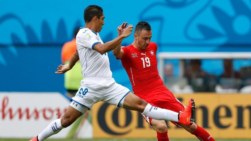 Honduras' Jorge Claros, left, tries to block a cross from Switzerland's Josip Drmic (19) during the group E World Cup soccer match between Honduras and Switzerland at the Arena da Amazonia in Manaus, Brazil, Wednesday, June 25, 2014. (AP Photo/Dolores Ochoa)