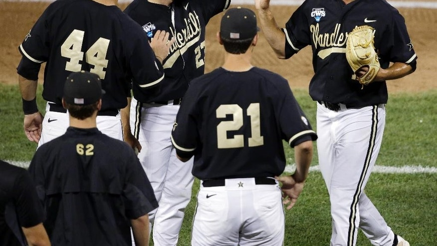 Vanderbilt pitcher Tyler Beede, right, leaves in the seventh inning of Game 2 of the best-of-three NCAA baseball College World Series finals against Virginia in Omaha, Neb., Tuesday, June 24, 2014. (AP Photo/Nati Harnik)
