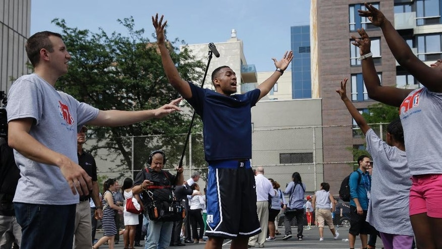 Duke's Jabari Parker, center, helps run drills during a basketball clinic in New York, Wednesday, June 25, 2014. Parker and other 2014 draft prospects are in town for the NBA draft in Brooklyn, New York on June 26, 2014. (AP Photo/Seth Wenig)