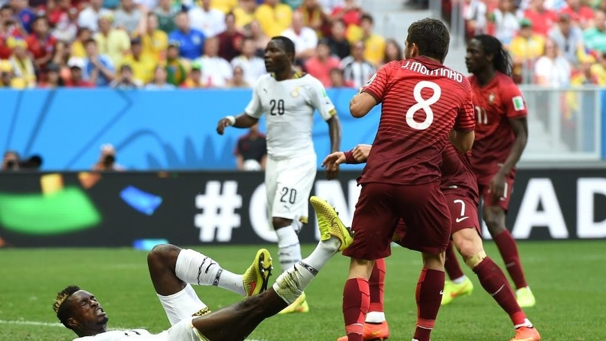 Ghana's John Boye, left, grimaces after scoring an own goal during the group G World Cup soccer match between Portugal and Ghana at the Estadio Nacional in Brasilia, Brazil, Thursday, June 26, 2014. (AP Photo/Paulo Duarte)