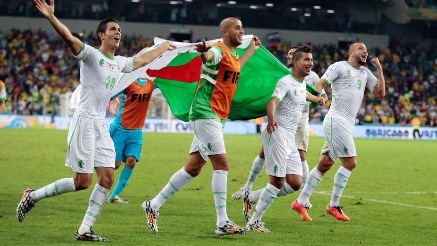 Algerian players celebrate after the group H World Cup soccer match between Algeria and Russia at the Arena da Baixada in Curitiba, Brazil, Thursday, June 26, 2014. The match ended in a 1-1 draw, but Algeria qualified for the round of 16. (AP Photo/Ivan Sekretarev)