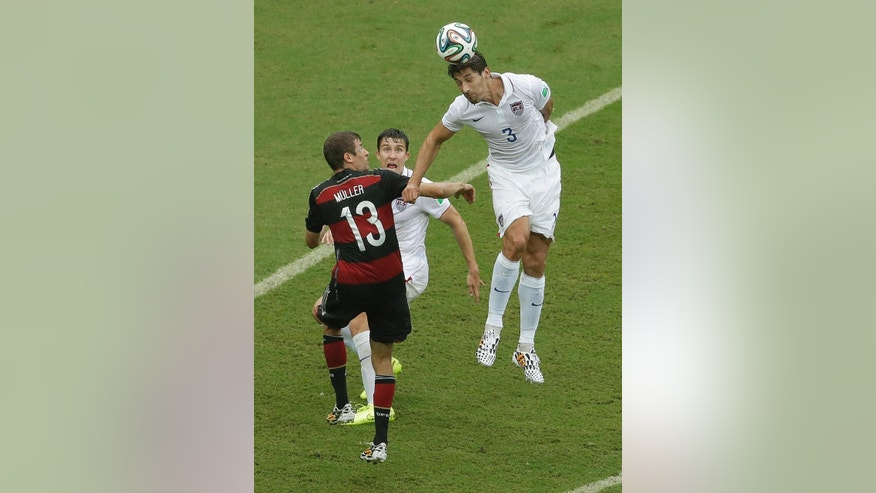 United States' Omar Gonzalez beds the ball over Germany's Thomas Mueller during the group G World Cup soccer match between the USA and Germany at the Arena Pernambuco in Recife, Brazil, Thursday, June 26, 2014. (AP Photo/Hassan Ammar)