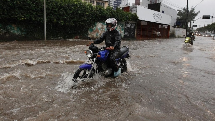 Motorcyclists make their way down a flooded street after heavy rain storms in Recife, Brazil, Thursday, June 26, 2014. The World Cup soccer match between the USA and Germany will be played at the Arena Pernambuco in Recife today.  (AP Photo/Petr David Josek)