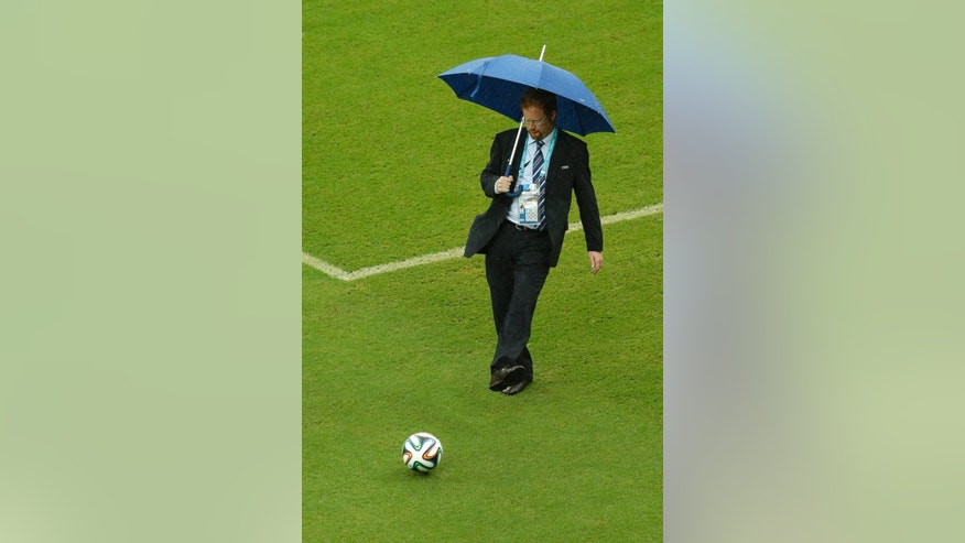 A FIFA official tests the pitch as rain pours down prior to the group G World Cup soccer match between the USA and Germany at the Arena Pernambuco in Recife, Brazil, Thursday, June 26, 2014. (AP Photo/Hassan Ammar)