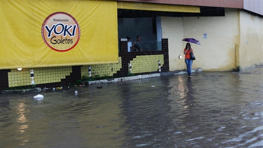 A woman waits on the sidewalk on a flooded street after heavy rain storms in Recife, Brazil, Thursday, June 26, 2014. The World Cup soccer match between the USA and Germany will be played at the Arena Pernambuco in Recife today.  (AP Photo/Petr David Josek)